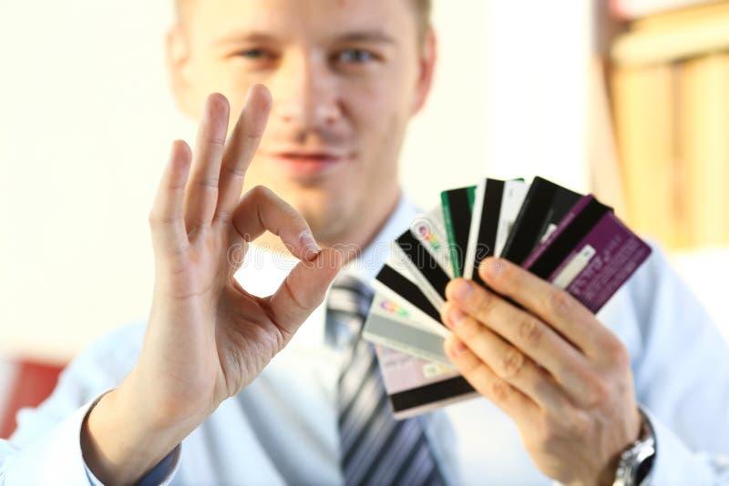 Het mannelijke wapen toont O.K. of bevestigt holdingsbos van creditcards stock foto's