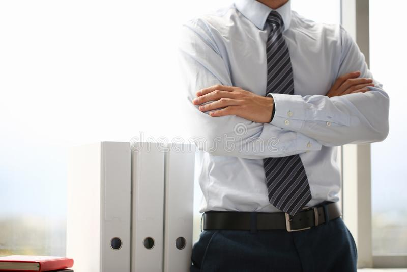 Het mannetje dient kostuum in dat op de achtergrond van de borstclose-up wordt gekruist stock foto