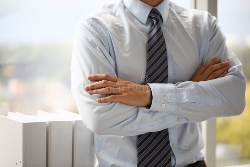 Het mannetje dient kostuum in dat op de achtergrond van de borstclose-up wordt gekruist stock foto's