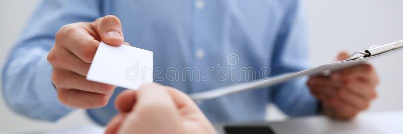 Het mannetje dient kostuum in geeft leeg visitekaartje stock fotografie