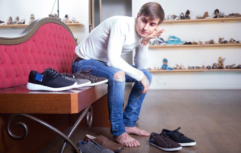 Het mannetje kiest de winterschoenen in een schoenopslag stock afbeelding