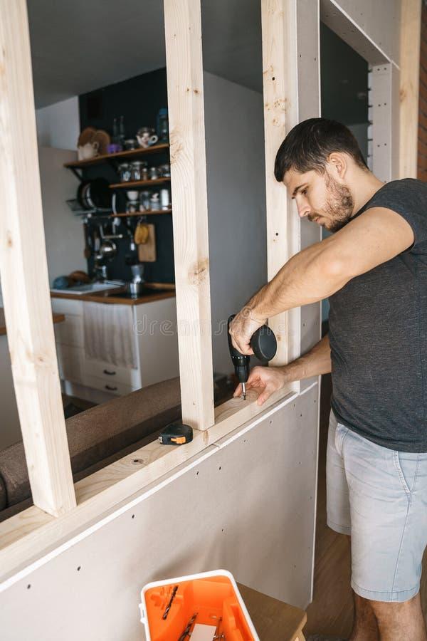 Het mannetje met een Schroevedraaier in zijn hand bevestigt een houten structuur voor een venster in zijn huis Reparatie zelf royalty-vrije stock afbeelding