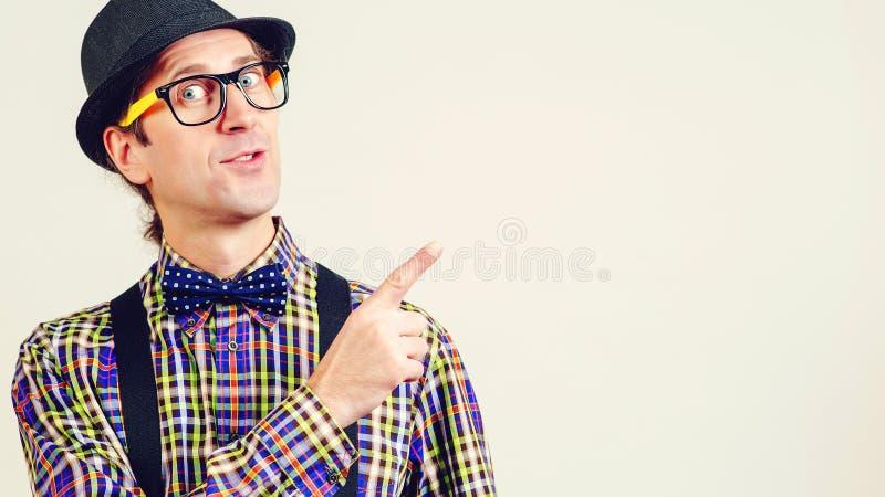 Het mannetje nerd in bril richt met duim op exemplaarruimte voor uw reclameinhoud Grappige nerd of geek op witte achtergrond royalty-vrije stock afbeelding