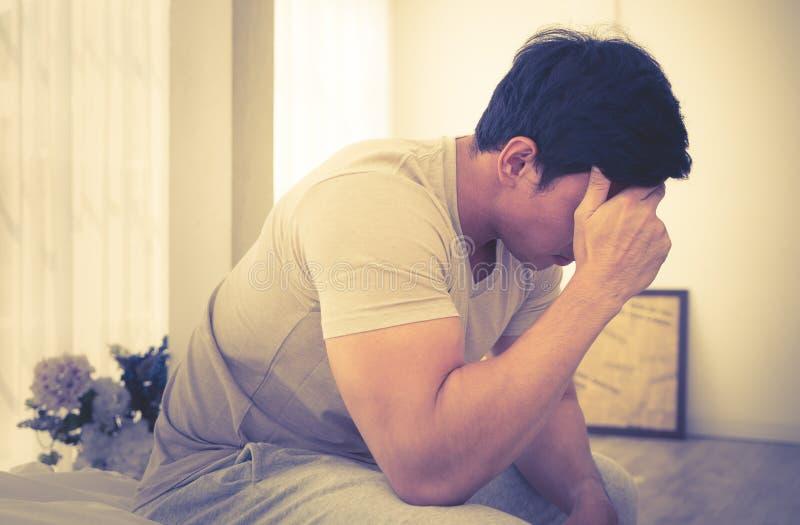 Het mannetje ontwaakte op bed met uit hoofdpijn en spanning royalty-vrije stock afbeelding