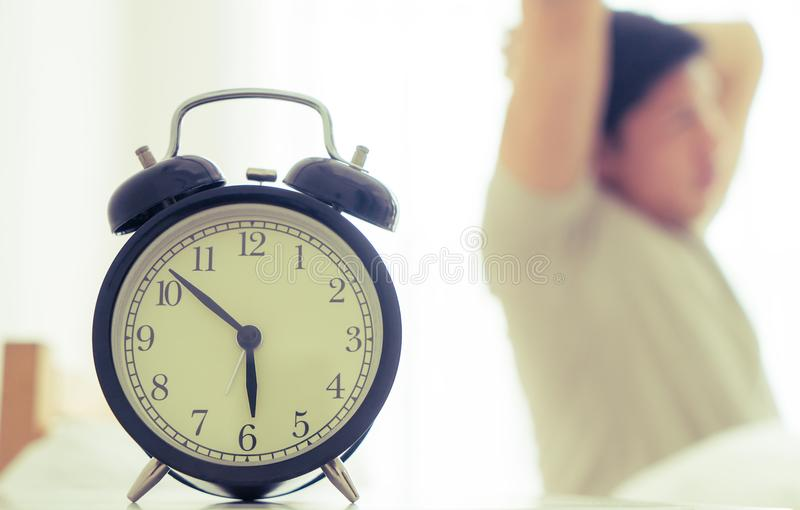 Het mannetje rekt uit uit na ontwaakte met wekker die zes o-klok tonen stock foto