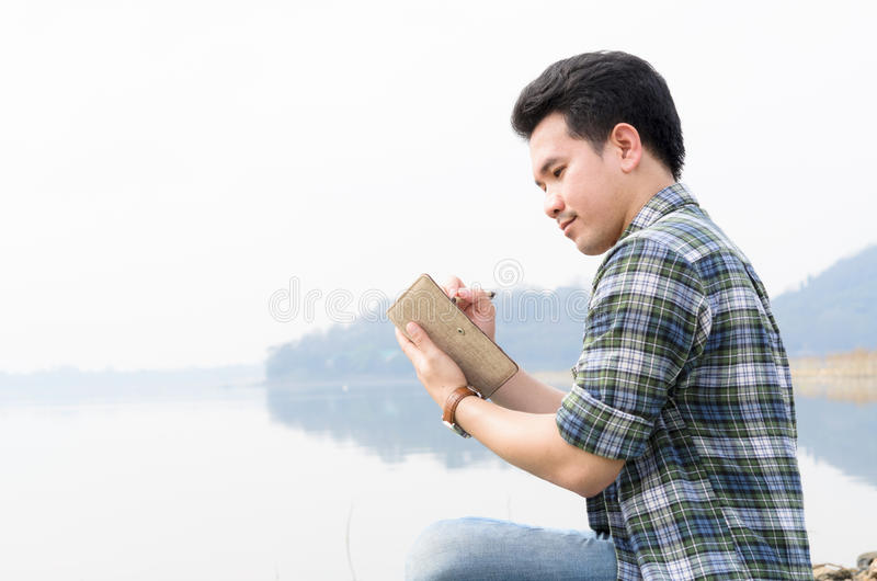 Het mannetje schrijft een boek in het park op een de zomersdag stock afbeelding