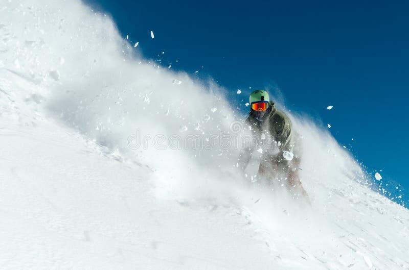 Het mannetje snowboarder boog en remmen die losse diepe sneeuw bespuiten royalty-vrije stock foto