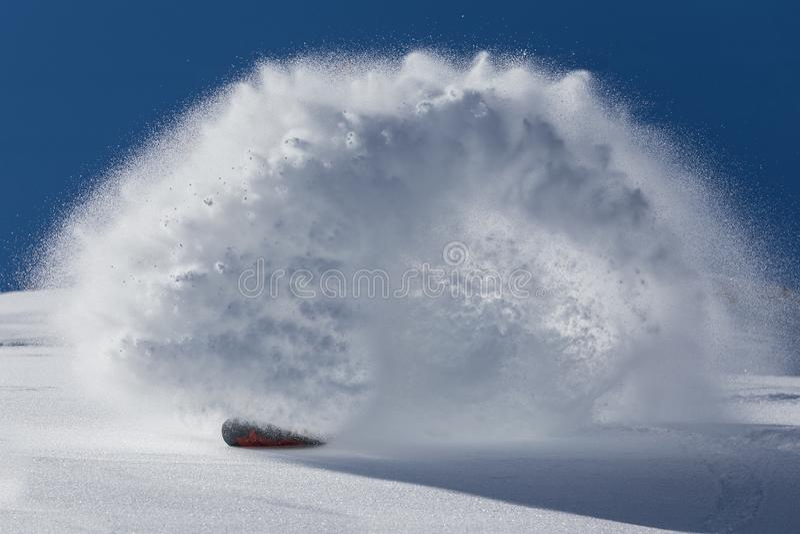 Het mannetje snowboarder boog en remmen die losse diepe sneeuw op de freeridehelling bespuiten royalty-vrije stock afbeelding