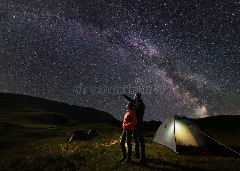 Het mannetje toont wijfje bij het gelijk maken van sterrige hemel bij Melkachtige manier tegen de achtergrond van bergen stock fotografie