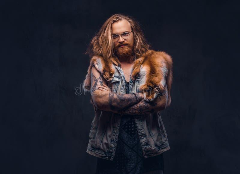 Het mannetje van het Tattoedroodharige hipster met lang luxuriant haar en volledige baard gekleed in een t-shirt en een jasje hou royalty-vrije stock afbeelding