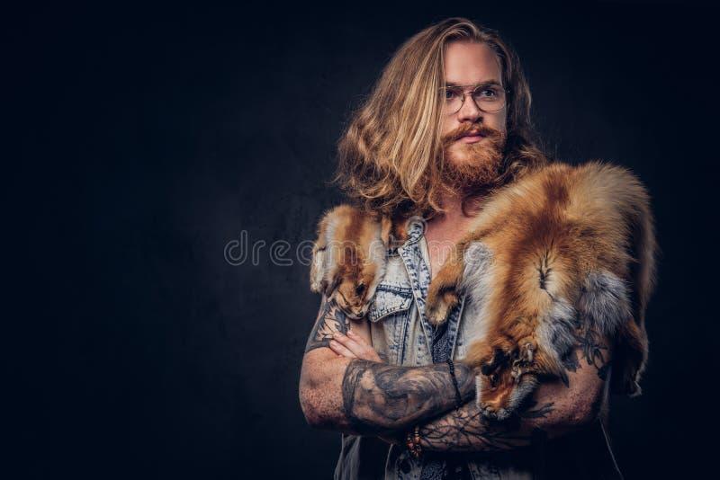 Het mannetje van het Tattoedroodharige hipster met lang luxuriant haar en volledige baard gekleed in een t-shirt en een jasje hou stock foto