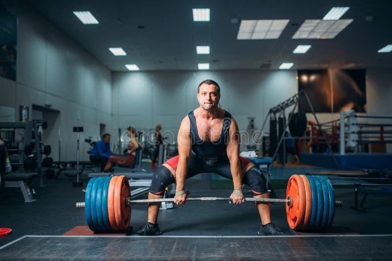Het mannetje weightlifter treft voorbereidingen om zware barbell te trekken stock foto
