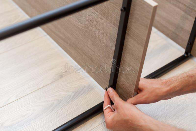 Het manusje van alles gebruikt hulpmiddelen voor meubilair om de plank op het boekenrek te bevestigen royalty-vrije stock fotografie