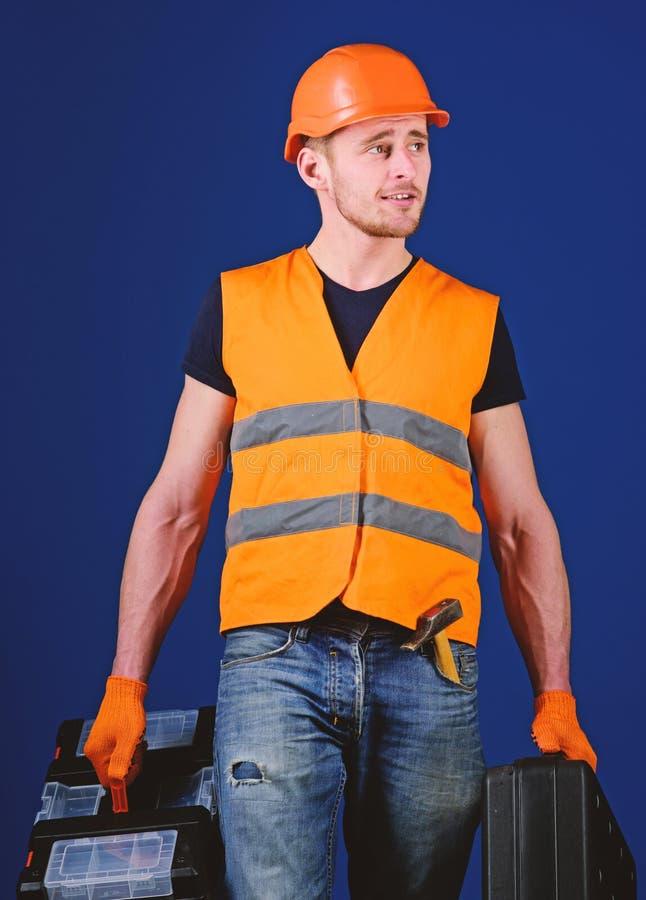 Het manusje van alles, hersteller op dromerig gezicht gaat en draagt zakken met beroepsuitrusting De mens in helm, bouwvakker hou stock foto's
