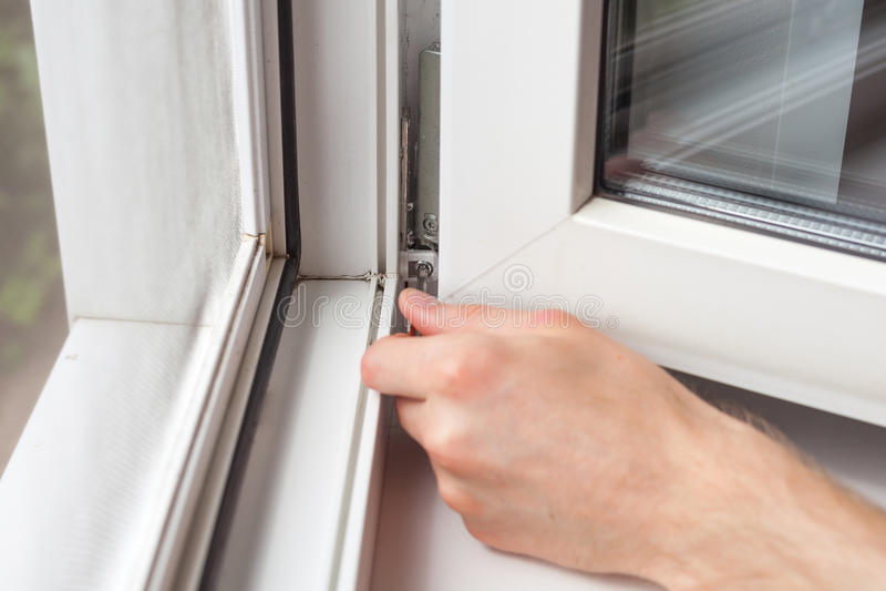 Het manusje van alles herstelt plastic venster met een zeshoek De werkman past de verrichting van het plastic venster aan royalty-vrije stock afbeelding
