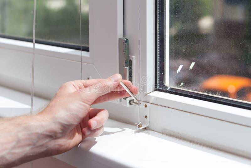 Het manusje van alles herstelt plastic venster met een zeshoek De werkman past de verrichting van het plastic venster aan stock afbeeldingen