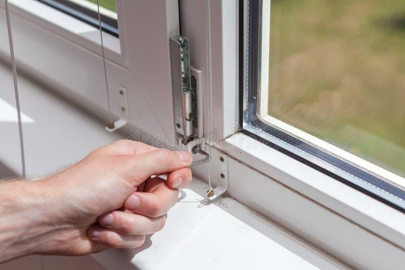 Het manusje van alles herstelt plastic venster met een zeshoek De werkman past de verrichting van het plastic venster aan royalty-vrije stock fotografie