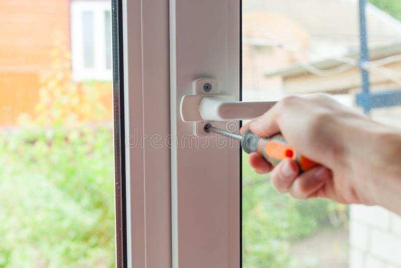 Het manusje van alles herstelt plastic venster met schroevedraaier De werkman past de verrichting van het plastic venster aan stock foto
