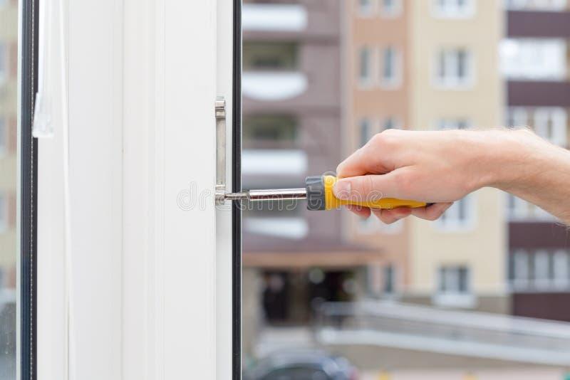 Het manusje van alles herstelt plastic venster met schroevedraaier De werkman past de verrichting van het plastic venster aan stock foto's