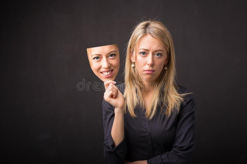 Het masker van de vrouwenholding van haar gelukkig gezicht royalty-vrije stock foto's