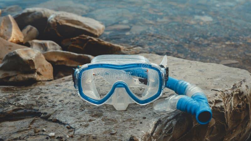 Het masker voor Freediver en snorkelt Leugen op het Strand, op de Rotsen Toerisme en reisconcept stock fotografie