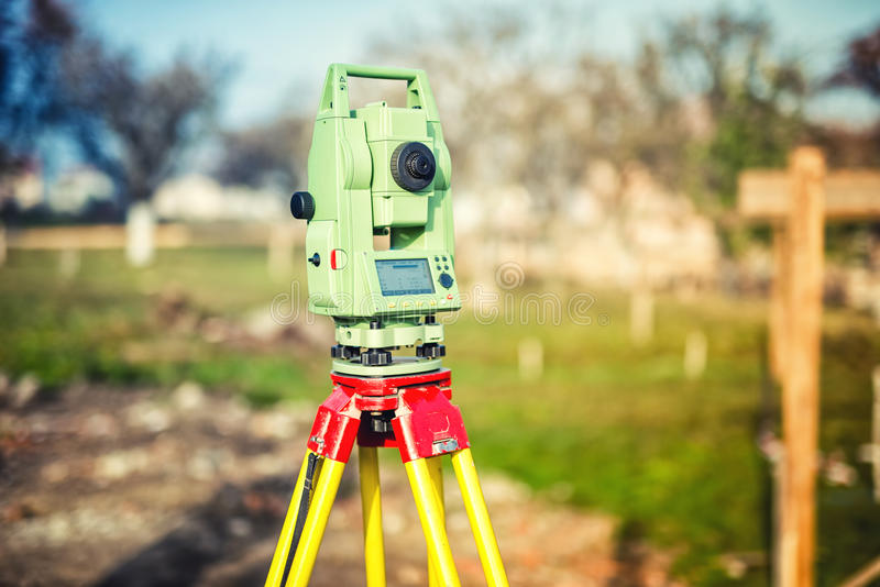Het materiaal van de landmeterstechniek met theodoliet en totale post bij een bouwwerf stock foto