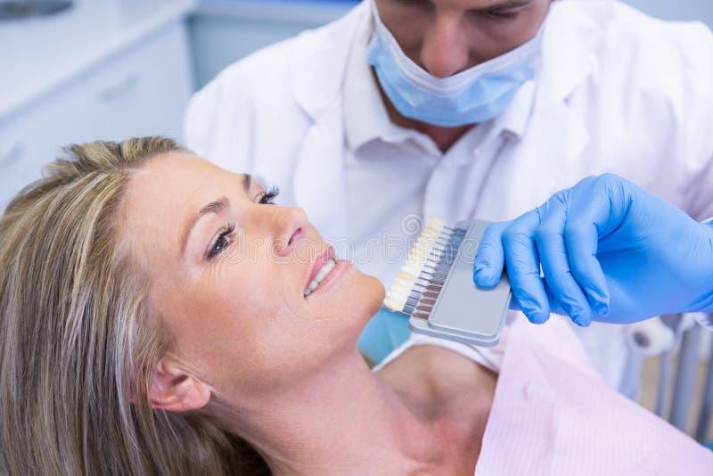Het materiaal van de tandartsholding terwijl het onderzoeken van patiënt bij kliniek stock foto's