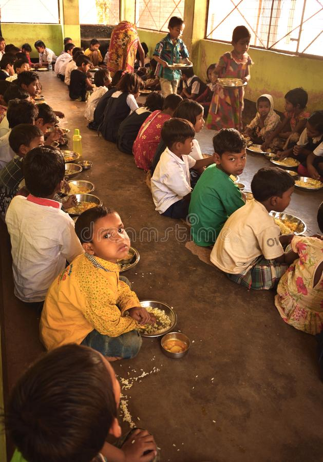 Het medio programma van de dagmaaltijd, een Indisch overheidsinitiatief, is lopend in een lage school De leerlingen nemen hun maa stock foto