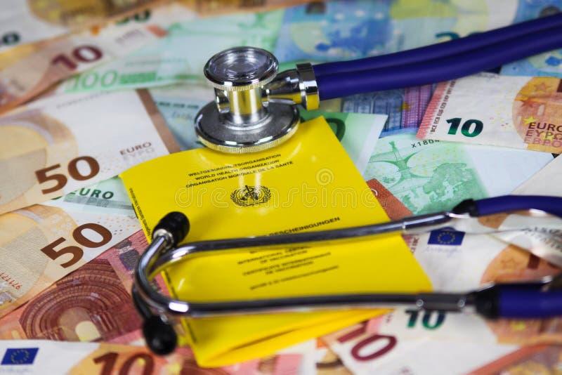 Het medische concept van inentingskosten - Stethoscoop en geel internationaal certificaat van inenting op Euro papiergeldbankbilj stock fotografie