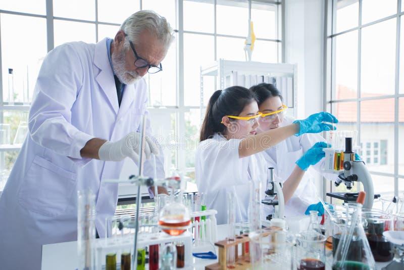 Het medische Onderzoek en de Wetenschappers werken met een microscoop en een tablet en Reageerbuizen, Micropipette en Analyseresu stock afbeeldingen