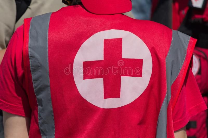 Het medische personeel in eenvormig met het teken van het Rode Kruis verleent medische hulp royalty-vrije stock fotografie