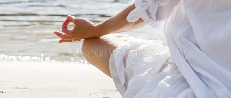 Het mediteren van de vrouw bij het overzees stock afbeelding