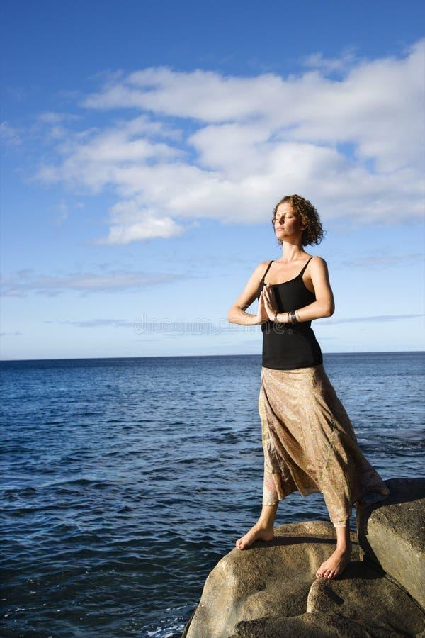 Het mediteren van de vrouw door oceaan. royalty-vrije stock foto