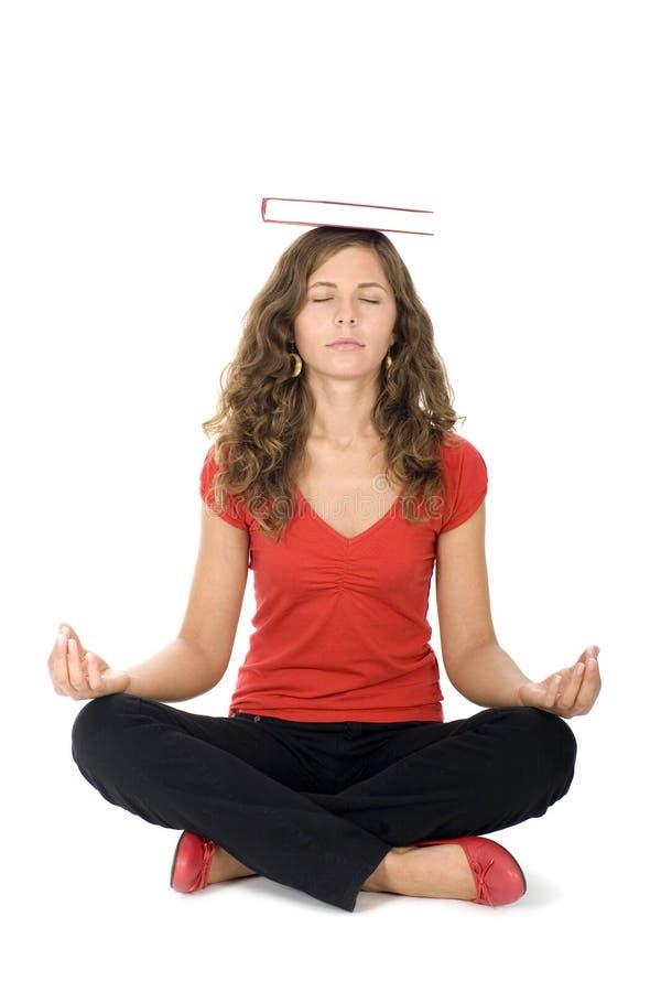Het mediteren van de vrouw met boek op hoofd stock foto
