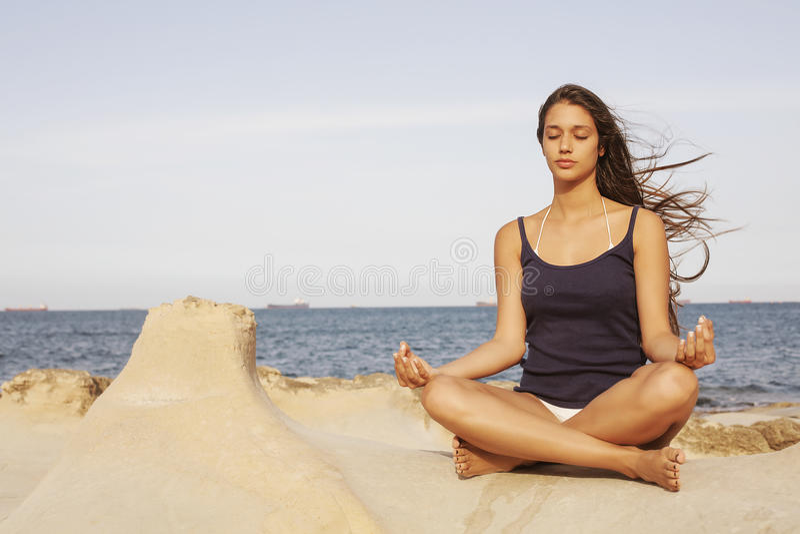 Het mediteren van de vrouw op het strand royalty-vrije stock afbeelding