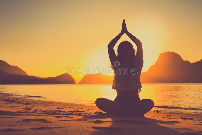 Het mediteren van vrouw door de oceaan met rotsen op de achtergrond bij zonsondergang stock foto