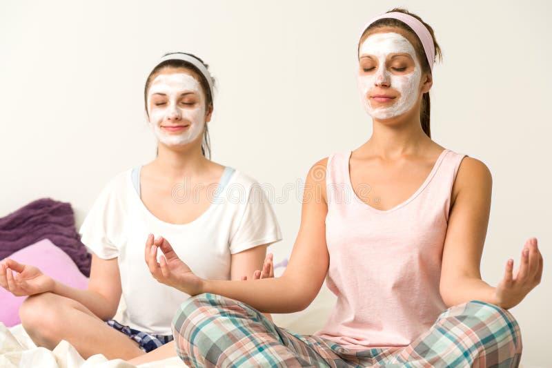 Het mediteren van vrouwen die wit gezichtsmasker dragen royalty-vrije stock afbeelding