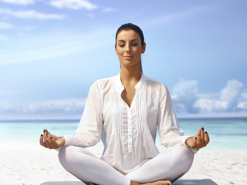 Het mediteren in vrede op de kust stock foto's