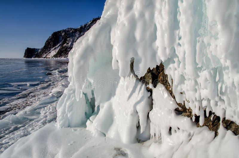 Het meer Baikal is behandeld met ijs en sneeuw, sterk koud, dik duidelijk blauw ijs De ijskegels hangen van de rotsen Het meer Ba royalty-vrije stock foto