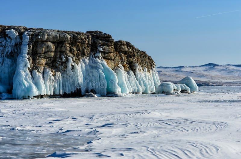 Het meer Baikal is behandeld met ijs en sneeuw, sterk koud, dik duidelijk blauw ijs De ijskegels hangen van de rotsen Het meer Ba royalty-vrije stock fotografie