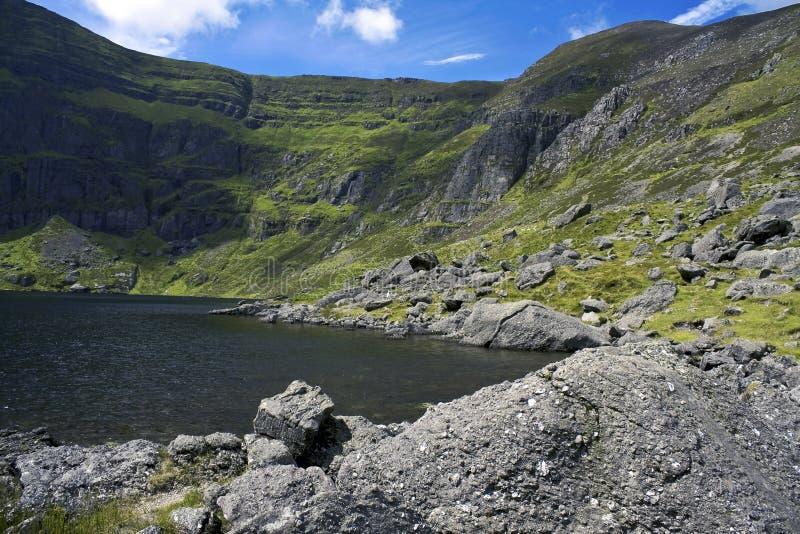 Het meer van de berg dat door klippen wordt omringd stock foto