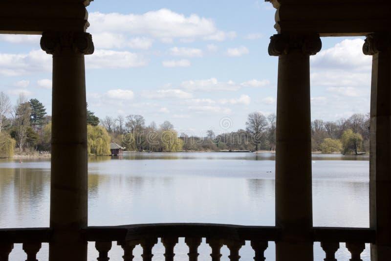 Het meer wordt gezien tussen silhoutted kolommen die royalty-vrije stock foto's