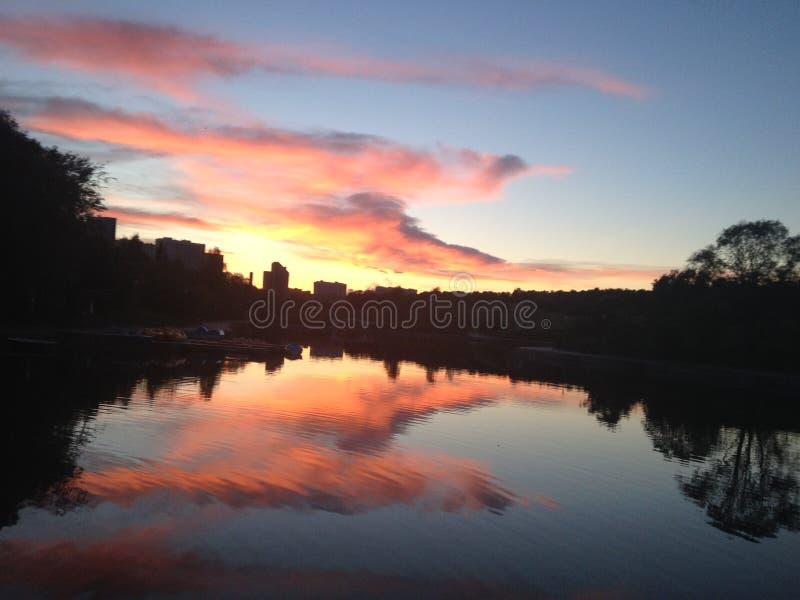 Het meerbezinning van de nachtwolk in het alarmrood van de waterhemel stock foto