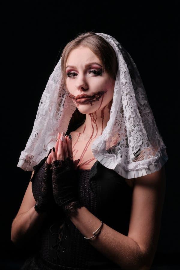 Het meisje in het beeld van een vreselijke non met een bloedige mond Make-up voor de viering van Halloween Kostuum voor een versc royalty-vrije stock foto's