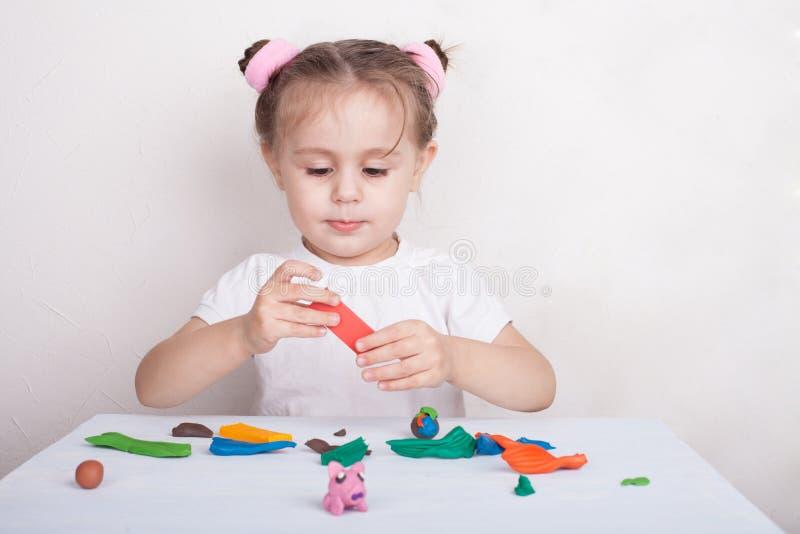 Het meisje beeldhouwt van plasticine roze varken stock foto