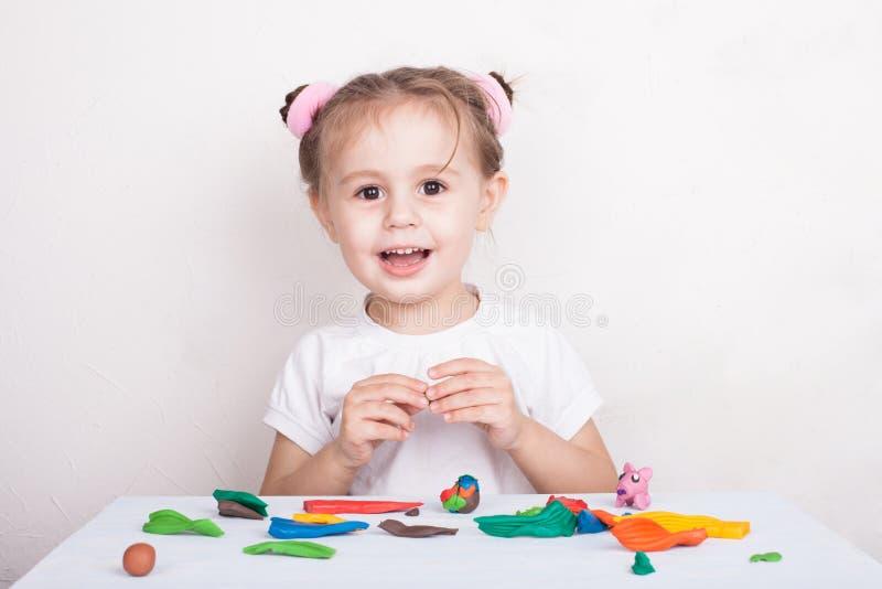Het meisje beeldhouwt van plasticinevarken en konijntje stock foto's