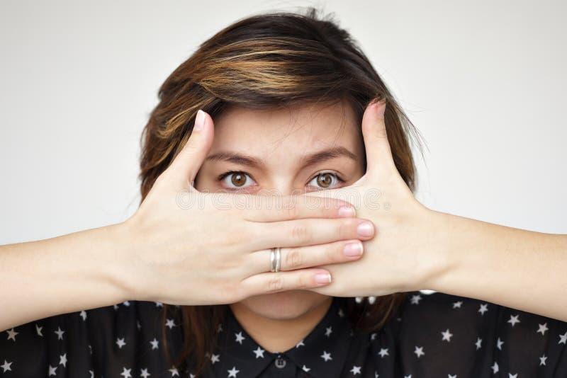 Het meisje behandelt haar gezicht met haar handen royalty-vrije stock fotografie