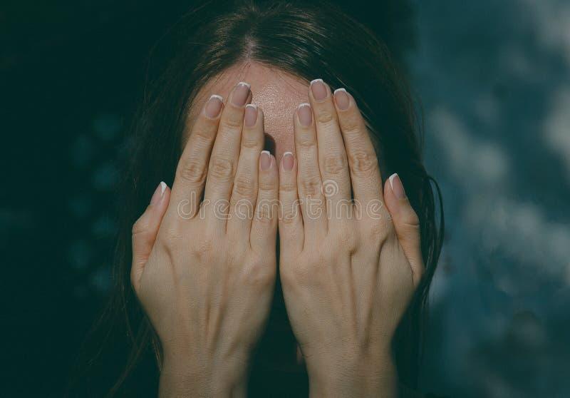 Het meisje behandelt haar gezicht met haar handen, gestemde foto stock foto's