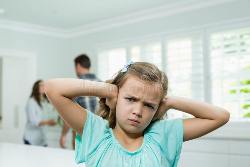 Het meisje behandelt haar oren met haar handen terwijl ouders die op achtergrond debatteren stock fotografie