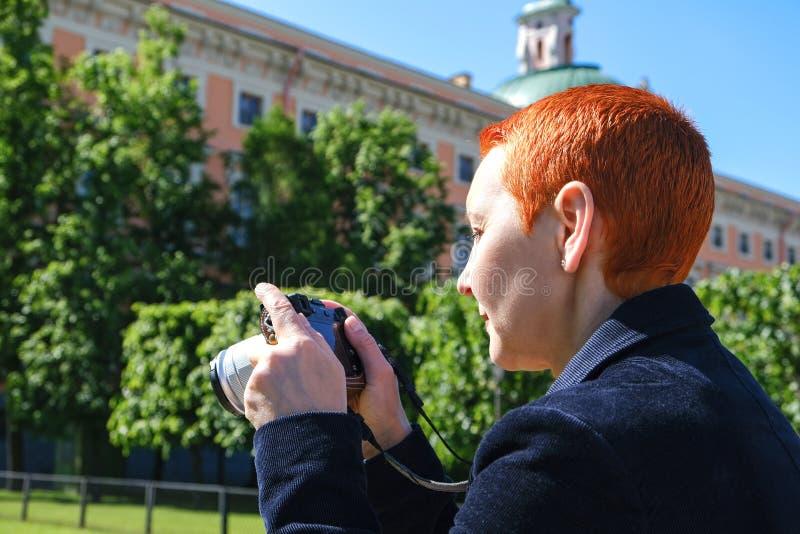 Het meisje bekijkt de foto's in de camera De emotie van blije verrassing Het korte kapsel van vrouwen Modieus modieus profiel royalty-vrije stock afbeelding